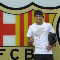 Photo - FILE - In this June 3, 2013 file photo, FC Barcelona's then new signing Neymar gestures upon his arrival at the club's office at the Camp Nou stadium in Barcelona, Spain. A Spanish court has charged Spanish league champion Barcelona with tax fraud of  euro 9.1 million ($12.5 million) over the transfer of Brazil forward Neymar. Judge Pablo Ruz said in his decision, released on Thursday, Feb. 20, 2014 there was enough evidence to merit charges over Neymar's 57 million-euro (then $77 million) move from Santos last summer. Thursday's decision comes a day after public prosecutor Jose Perals charged Barcelona with fabricating simulated contracts and using