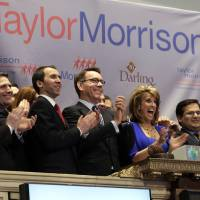 Photo - Sheryl Palmer, President and CEO of Taylor Morrison, joined by members of the company's management team, applauds during opening bell ceremonies of the New York Stock Exchange, as they celebrate the company's IPO, Wednesday, April 10, 2013. Stocks are opening higher on Wall Street, a day after the Dow Jones industrial average closed at its second all-time high in a week. (AP Photo/Richard Drew)