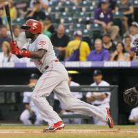 Photo - Cincinnati Reds' Brandon Phillips, left, follows the flight of his RBI-triple with Colorado Rockies catcher Wilin Rosario in the first inning of a baseball game in Denver on Saturday, Aug. 31, 2013. (AP Photo/David Zalubowski)