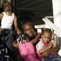 Photo - In a Wednesday, Oct. 2, 2013 photo, Patricia Jones, 34, center, is hugged by her 4-year-old daughter Pashalae Armstrong, 4, center left, while talking to The Associated Press outside of her home in Newark, N.J., with her other children, Nature Harris, 15, top, and  Latrell Armstrong, 2, right. Jones was denied getting a proof printout of Harris' disability to apply for government aid because the shutdown has closed her local social security office. Like millions of other low-income women, Jones relies on the federal Women, Infants and Children program to pay for infant formula _ a program that's now jeopardized by the federal government shutdown. New Jersey and other states say they have enough money to operate the program for another few weeks, but advocates worry what will happen next. (AP Photo/Julio Cortez) Jones was denied getting a proof printout of Harris' disability to apply for government aid because the shutdown has closed her local social security office. Like millions of other low-income women, Jones relies on the federal Women, Infants and Children program to pay for infant formula _ a program that's now jeopardized by the federal government shutdown. New Jersey and other states say they have enough money to operate the program for another few weeks, but advocates worry what will happen next. (AP Photo/Julio Cortez)