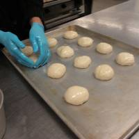 Photo - Volunteer Susan Harroz places bread dough on a baking sheet at St. Elijah Antiochian Orthodox Christian Church.