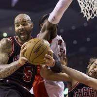 Photo - Chicago Bulls' Carlos Boozer (5) claims a rebound in front of Toronto Raptors' Patrick Patterson and Bulls' Joakim Noah during the first half of an NBA basketball game, Wednesday, Feb. 19, 2014 in Toronto. (AP Photo/The Canadian Press, Chris Young)