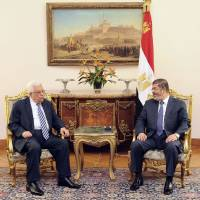Photo -   In this photo, released by the Egyptian Presidency, Palestinian President Mahmoud Abbas, left, meets with Egyptian President Mohammed Morsi, right, in Cairo Egypt, Tuesday, Nov. 13, 2012. In a meeting in Cairo Tuesday with Western-backed Palestinian President Mahmoud Abbas, Morsi expressed his