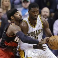 Photo - Atlanta Hawks forward Josh Smith, left, tries to knock the ball away from Indiana Pacers center Roy Hibbert in the first half of an NBA basketball game in Indianapolis, Tuesday, Feb. 5, 2013. (AP Photo/Michael Conroy)