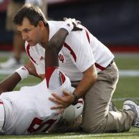 Photo -   Indiana quarterback Tre Roberson (5) reaches up to a team trainer as they wait for an ambulance to come onto the field after he was hurt on a red zone run during their NCAA college football game against Massachusetts in Foxborough, Saturday, Sept. 8, 2012. (AP Photo/Stephan Savoia)