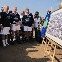 Photo -   Former members of Uruguay's rugby team who survived a 1972 plane crash in the Chilean Andes hold a minute of silence after the unveiling a plaque with pictures of family members and friends who died in the crash, in Santiago, Chile, Saturday, Oct. 13, 2012. Uruguay's former rugby players marked the 40 year anniversary since they survived 72 days in the Chilean Andes by playing a rugby match with the former members of Chile's team. Only 16 of the 45 passengers aboard survived, by feeding on dead passengers preserved in the snow. (AP Photo/Luis Andres Henao)