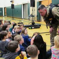 Photo - FILE - In this file photo of Jan. 28, 2013, Capt. Bryn Reynolds of the Washington County Sheriff's Office takes a question from a student at the Hudson Falls Primary School in Hudson Falls, N.Y. Reynolds and other officers were present to show off their equipment and discuss safety and to practice drills with unloaded guns to prepare for armed intruders at the school. School security has come under more scrutiny in the wake of the Sandy Hook Elementary School massacre in Newtown, Conn., that killed 26 people in December. (AP Photo/The Post-Star, Omar Ricardo Aquije, File)