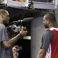 Photo - Miami Heat small forward LeBron James, left, points a video camera at shooting guard Dwyane Wade after a news conference following basketball practice on Saturday, June 8, 2013, at the American Airlines Arena in Miami. The Heat and the San Antonio Spurs are to play Game 2 of the NBA Finals, Sunday. (AP Photo/Wilfredo Lee)