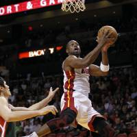 Photo -   Miami Heat's Dwyane Wade (3) goes to the basket as Milwaukee Bucks' Ersan Ilyasova, left, defends during the first half of an NBA basketball game, Wednesday, Nov. 21, 2012, in Miami. (AP Photo/Alan Diaz)