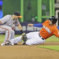 Photo - Miami Marlins' Giancarlo Stanton steals second base as San Francisco Giants second baseman Marco Scutaro is unable to make the tag during the first inning of a baseball game, Sunday, July 20, 2014 in Miami. (AP Photo/Wilfredo Lee)