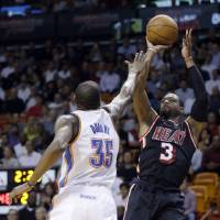 Photo - Miami Heat guard Dwyane Wade (3) shoots over Oklahoma City Thunder small forward Kevin Durant (35) during the second  period of an NBA basketball game in Miami, Wednesday, Jan. 29, 2014. (AP PhotoAlan Diaz)
