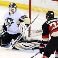 Photo - Pittsburgh Penguins goaltender Tomas Vokoun (92) makes a pad save as Ottawa Senators' Guillaume Latendresse (73) looks onduring the second period of their NHL hockey game in Ottawa, Ontario, Monday, April 22, 2013. (AP Photo/The Canadian Press, Fred Chartrand)