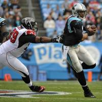 Photo - Carolina Panthers' Cam Newton (1) scrambles for a gain as Atlanta Falcons' Vance Walker (99) chases during the first half of an NFL football game in Charlotte, N.C., Sunday, Dec. 9, 2012. (AP Photo/Rainier Ehrhardt)