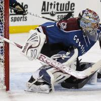 Photo - Colorado Avalanche goalie Semyon Varlamov, of Russia, makes a glove save of a shot against the Nashville Predators in the second period of an NHL hockey game in Denver on Saturday, March 30, 2013. (AP Photo/David Zalubowski)