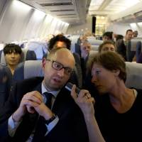 Photo - Ukraine's Prime Minister Arseniy Yatsenyuk, left, speaks with Cathrin Kahlweit, a correspondent at the Suddeutsche Zeitung, as he travels aboard a commercial flight from Kiev to Vienna, enroute to Brussels for a European People's Party summit, Wednesday, March 19, 2014. Yatsenyuk has declared the recent violence as pro-Russian military forces took control of some military facilities in Crimea, showed the conflict has gone beyond the
