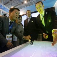 Photo - The Governor of Tokyo Naoki Inose, left, examines the stand presenting Istanbul as a candidate for 2020 Olympic at the SportAccord International Convention in St. Petersburg, Russia, Wednesday, May 29, 2013. (AP Photo/Dmitry Lovetsky)