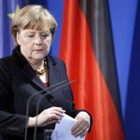 Photo - German Chancellor Angela Merkel arrives for a statement at the chancellery in Berlin, Germany, Monday, Feb. 11, 2013. Merkel says she has the