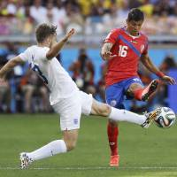 Photo - England's Luke Shaw, left, challenges Costa Rica's Cristian Gamboa during the group D World Cup soccer match between Costa Rica and England at the Mineirao Stadium in Belo Horizonte, Brazil, Tuesday, June 24, 2014. (AP Photo/Matt Dunham)