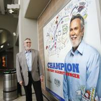 Photo - The Regional Food Bank of Oklahoma is one of six nonprofit agencies to be featured in Chesapeake Energy Corp.'s Cheering for Champions campaign. Executive Director Rodney Bivens stands near a sign bearing his picture Wednesday at Chesapeake Energy Arena. Photo by PAUL B. SOUTHERLAND, The Oklahoman