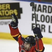 Photo - Florida Panthers' Scottie Upshall (19) celebrates after Tom Gilbert scored a goal against the Toronto Maple Leafs during the second period of an NHL hockey game in Sunrise, Fla., Tuesday,  Feb. 4, 2014. (AP Photo/J Pat Carter)