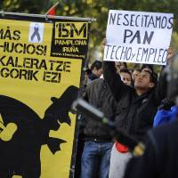 Photo -   A man who identified himself as Edwin, 32, from Ecuador, right, who was evicted from his home over debts, holds up banner reading ''We need bread, roof and employment'' beside a poster to support people fighting against evictions reading, ''No More Evictions'', in front of Spanish riot police during a general strike against government austerity measures, in Pamplona, northern Spain, Wednesday, Nov. 14, 2012. A Spanish Interior Ministry official says 32 people have been arrested and 15 people treated for minor injuries in disturbances as a general strike in Spain against austerity measures and economic reforms began. The General Workers Union said the nationwide stoppage, the second this year, was being heeded by nearly 100 percent of workers Wednesday in the automobile, energy, shipbuilding and constructions industries. (AP Photo/Alvaro Barrientos)