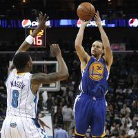 Photo - Golden State Warriors guard Stephen Curry (30) shoots over New Orleans Hornets guard Roger Mason Jr. (8) during the first half of an NBA basketball game in New Orleans, Saturday, Jan. 19, 2013. The Warriors won 116-112. (AP Photo/Jonathan Bachman)