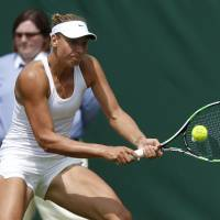 Photo - Belgium's Yanina Wickmayer plays a return to Australia's Samantha Stosur during their first round match at the All England Lawn Tennis Championships in Wimbledon, London,  Monday, June  23, 2014. (AP Photo/Sang Tan)