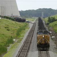 Photo - In this photo taken June 2, 2014, a locomotive pulling coal cars is stopped near the White Bluff power plant near Redfield, Ark. The Arkansas Public Service Commission has scheduled a June 25 meeting to explore options for complying with a newly proposed federal air rule regulating carbon dioxide emissions from existing power plants. (AP Photo/Danny Johnston)