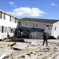 Photo -   People survey damage to beachfront houses in Long Beach Island, N.J., Wednesday, Oct. 31, 2012. New Jersey received the brunt of superstorm Sandy, which made landfall in the state and killed six people. More than 2 million customers were without power as of Wednesday afternoon, down from a peak of 2.7 million. (AP Photo/Philadelphia Inquirer, Ed Hille) PHIX OUT; TV OUT; MAGS OUT; NEWARK OUT