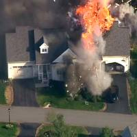 Photo - In this frame grab from television helicopter video, a police SWAT team, left, is parked on the lawn of a home in Brentwood, N.H., as it explodes in flames, Monday May 12, 2014.  Shots were fired just before the fire, which involved a police officer, according to the New Hampshire State Police. (AP Photo/WCVB-TV 5) TV OUT