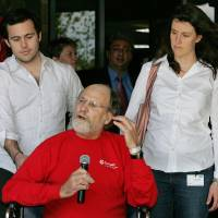 Photo - FILE - In this April 30, 2007, file photo, son Jeffrey Corzine, left, and daughter Jennifer Corzine-Pisani, listen as New Jersey Gov. Jon S. Corzine addresses the media outside Cooper University Hospital in Camden, N.J., as he was released after being hospitalized for serious injuries in an automobile accident on April 12. A spokesman for the former governor announced on Thursday, March 13, 2014, that Jeffrey Corzine had died at age 31. There were no other details available. (AP Photo/Mel Evans, File)