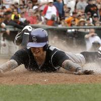Photo - Colorado Rockies' Brandon Barnes slides home on his two-run inside-the-park home run off San Francisco Giants pitcher Sergio Romo during the ninth inning of a baseball game in San Francisco, Saturday, June 14, 2014. (AP Photo/Jeff Chiu)
