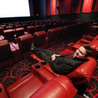 Photo - Ryan Noonan, a spokesman for AMC Theatres, demonstrates the new power reclining chairs at the Penn Square Mall theater.  PAUL B. SOUTHERLAND - PAUL B. SOUTHERLAND