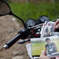 Photo -   CORRECTS LAST NAME SPELLING AND ADDS FIRST NAME 'EBED' - In this Oct 17, 2012 photo, Wilfredo Yanes, reflected on a mirror of his motorcycle, shows pictures of his late son Ebed Jaasiel Yanes, 15, at the site where he was shot dead allegedly by soldiers in Tegucigalpa, Honduras. According to his relatives, Yanes was killed by soldiers early Sunday, May 27, when he was riding a motorcycle, near a military checkpoint. (AP Photo/Esteban Felix)