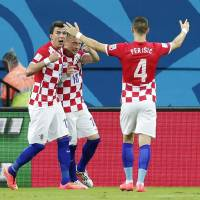 Photo - Croatia's Ivica Olic (18) celebrates with his teammates after scoring his side's first goal during the group A World Cup soccer match between Cameroon and Croatia at the Arena da Amazonia in Manaus, Brazil, Wednesday, June 18, 2014.  (AP Photo/Marcio Jose Sanchez)