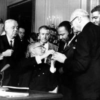 Photo - FILE 0 In this July 2, 1964, file photo, President Lyndon B. Johnson reaches to shake hands with Dr. Martin Luther King Jr. after presenting the civil rights leader with one of the 72 pens used to sign the Civil Rights Act in Washington. Surrounding the president, from left, are, Rep. Roland Libonati, D-Ill., Rep. Peter Rodino, D-N.J., Rev. King, Emanuel Celler, D-N.Y., and behind Celler is Whitney Young, executive director of the National Urban League. President Barack Obama was 2-years-old when Johnson signed the Civil Rights Act. Half a century later, the first black president will commemorate what's been accomplished in his lifetime. He'll also recommit the nation to fighting deep inequalities that remain.  (AP Photo)