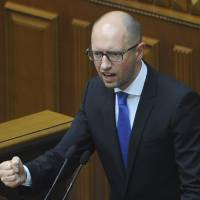 Photo - Ukrainian Prime Minister Arseniy Yatsenyuk speaks in the parliament in Kiev, Ukraine, Thursday, July 24, 2014. Arseniy Yatsenyuk announced his resignation Thursday, a move that opens the way for new elections that would reflect a the country's starkly changed political scene after the ouster of pro-Russian President Viktor Yanukovych in February. (AP Photo/Andrew Kravchenko, Pool)