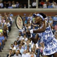 Photo - Venus Williams, of the United States, returns a shot to Timea Bacsinszky, of Switzerland, during the second round of the U.S. Open tennis tournament Wednesday, Aug. 27, 2014, in New York. (AP Photo/Jason DeCrow)