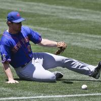 Photo - New York Mets second baseman Daniel Murphy chases down a base hit by San Diego Padres' Chris Nelson in the second inning of a baseball game Sunday, July 20, 2014, in San Diego.  (AP Photo/Lenny Ignelzi)
