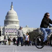 Photo - A man rides a bicycle as others walk on the National Mall Sunday, Jan. 20, 2013, with the U.S. Capitol prepared for the ceremonial swearing-in of President Barack Obama, the 57th Presidential Inaugural on Monday in Washington. (AP Photo/Alex Brandon)