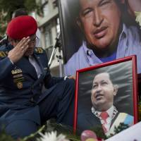 Photo - A Venezuelan army officer salutes a photo of Venezuela's late President Hugo Chavez at a makeshift memorial outside the Venezuelan Embassy in Buenos Aires, Argentina on Saturday, March 9, 2013. Chavez died on March 5, 2013 after a nearly two-year bout with cancer. (AP Photo/Victor R. Caivano)