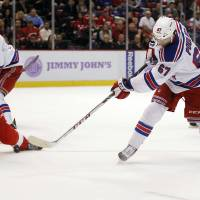 Photo - New York Rangers left wing Benoit Pouliot (67) takes a shot against Detroit Red Wings defenseman Niklas Kronwall (55), of Sweden, during the first period of an NHL hockey game Saturday, Oct. 26, 2013, in Detroit. (AP Photo/Duane Burleson)