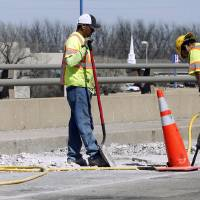 Photo - Workers repair a deteriorating section of the Lindsey Street bridge at Interstate 35 in Norman. PHOTO BY STEVE SISNEY, THE OKLAHOMAN  STEVE SISNEY