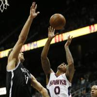 Photo - Atlanta Hawks point guard Jeff Teague (0) is defended by Brooklyn Nets center Brook Lopez (11) while going to the basket in the first half of an NBA basketball game on Wednesday, Jan. 16, 2013, in Atlanta. (AP Photo/John Bazemore)