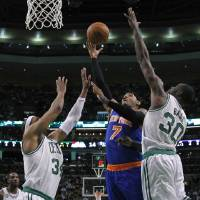 Photo - New York Knicks forward Carmelo Anthony (7) shoots against Boston Celtics forwards Paul Pierce (34) and Brandon Bass (30) during the first half in Game 4 of a first-round NBA basketball playoff series in Boston, Sunday, April 28, 2013. (AP Photo/Elise Amendola)
