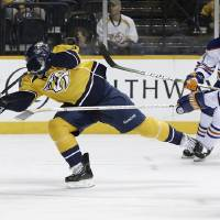 Photo - Nashville Predators right wing Chris Mueller, left, shoots and scores against the Edmonton Oilers as Ryan Smyth (94) and Corey Potter (44) give chase in the second period of an NHL hockey game on Monday, March 25, 2013, in Nashville, Tenn. (AP Photo/Mark Humphrey)