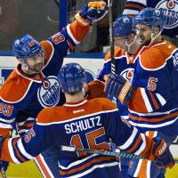 Photo - Edmonton Oilers' Sam Gagner (89), Nick Schultz (15), Ales Hemsky (83) and Mark Fraser (5) celebrate a goal against the Ottawa Senators during the second period of an NHL hockey game, Tuesday, March 4, 2014 in Edmonton, Alberta. (AP Photo/The Canadian Press, Jason Franson)