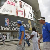 Photo - Tony Mussatto, at right, and his son, Joe Mussatto, 18, of Oklahoma City walk past the front of the arena before Game 4 of the NBA Finals between the Oklahoma City Thunder and the Miami Heat at American Airlines Arena, Tuesday, June 19, 2012. Photo by Bryan Terry, The Oklahoman