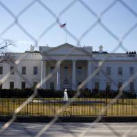 Photo - In this March 4, 2013, photo, The White House is seen through a chain-link fence where the inaugural reviewing stand once stood in Washington. Automatic spending cuts that took effect last Friday are expected to touch a vast range of government services. The Obama administration is canceling tours of the White House beginning Saturday, March 9, citing staffing reductions prompted by automatic budget cuts that began to take effect last Friday.  (AP Photo/Pablo Martinez Monsivais)