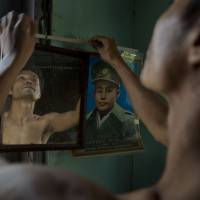 Photo - In this March 25, 2013 photo, San Zaw Htwe adjusts a portrait of Independence hero Gen. Aung San in his room in Yangon, Myanmar. The former political prisoner will turn 39 on Saturday, March 30, the second anniversary of the day President Thein Sein took office and pledged to transform Myanmar from a military dictatorship to a free-market democracy. Thein Sein's administration has made remarkable progress toward that goal, but at a price that San Zaw Htwe knows only too well: forgetting the past. (AP Photo/Gemunu Amarasinghe)